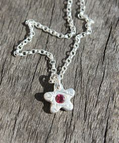 Silver ankle bracelet featuring a tiny silver flower charm. The flower charm is set with a garnet. Very pretty for wearing on the beach! By Little Silver Hedgehog