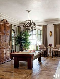 The great room is centered by the billiard table and unique light fixture | archdigest.com