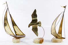 "Lot 732: Mid-Century Brass and Agate Sculptures; Three signed items with two depicting sailboats and a ""Yosi"" signed seagull; having cut and burnt brass cut-out images mounted into agate stones"
