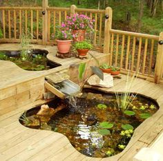 """This deck has two ponds in it. The ponds are made of rigid plastic tubs, set into """"sandboxes"""" under the deck. The deck boards were cut to follow the edges of the tubs. All together, the two tubs hold about 500 gallons of water and contain 18 large goldfish. A waterfall connects the higher tub to the lower one."""