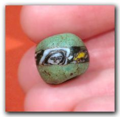 Green glass, the central section with naturalistic faces detailed in black and white, one bead with a black band around.  Material : Glass  Culture : Roman, c. 1st Century B.C. Condition : Intact