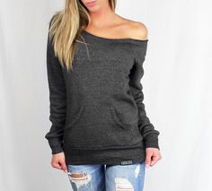 """A raw-edge, off-the-shoulder neckline and kangaroo front pocket give this cozy sweatshirt its vintage-inspired appeal. Made of our natural fleece alternative, it's the perfect way to stay warm in style.  <b>PRODUCT:</b> """"Off-The-Shoulder"""" <b>COLOR:</b>  Eco-Black <b>ART:</b>  Embroidered """"Luc..."""