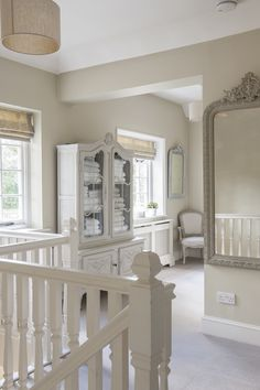 French-style touches include this pretty armoire on the upstairs landing