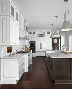 Large white kitchen boasts an exquisite dark brown island topped with white marble countertops holding a farmhouse sink fitted with a polished nickel gooseneck faucet illuminated by three Lily Hanging Shades.