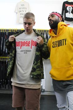 Justin Bieber wearing Bape 1st Camo College Coach Jacket in Green, Purpose Tour VFiles T-Shirt and Yeezy Supply Shorts in Cognac