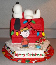 - House, Snoopy & bottom cake are all cake iced in buttercream.Snoopy is covered in fondant. Charlie Brown is edible image layed on fondant & attached to popsicle stick. Tree is fondant on wire &  painted with food color. Lights on house are fondant. Lights on sides are purchased Chocolate covered sunflower seeds.