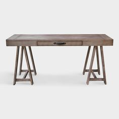 Handcrafted by Indonesian artisans, our solid mahogany wood desk is a rustic statement piece for your home office. Resting on a sawhorse base, its sleek top features a drawer with a black leather handle, all in a versatile gray finish.