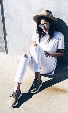 White distressed jeans, white t-shirt, sneakers, and a felt hat