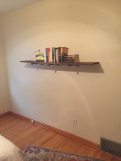 DIY floating book shelf made from reclaimed wood and metal pegs.