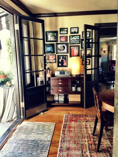 Classic black trim, French doors, wood and worn rugs