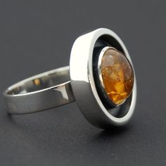 How beautiful is this citrine! Yellow with an inner texture like honey, love it! This ring is modern, sleek and highly polished to a mirror shine. I oxidised it for a beautiful contrast in the wall all around the 11mm stone. this ring is ready to ship in size 7 3/4. Please contact