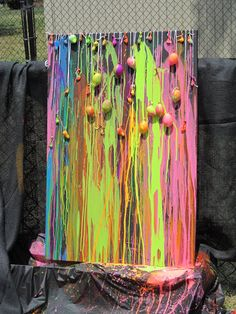 Water balloon dart painting. Need water balloons, metal darts, tempura paint, water, water bottles with sports caps, string, canvas, and drip cloth. Activity to do with the boys!