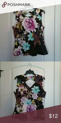 No sleeve blouse with a small diamond shape cutout Sleeveless top with a small diamond shaped cut out at base of neck.  Peplum style.  Black base color with various floral print.  Never worn. Worthington Tops Blouses
