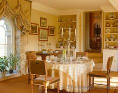 skirted table before arched window in this soft apricot dining room ~ Gervase Jackson-Stops home in England