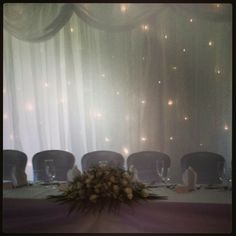 Wedding top table set up.  White chair covers with lilac organza sashes, swagging, fresh flower arrangment and starlight backdrop.