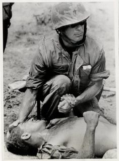 A U.S. Navy chaplain gives comfort to a wounded member of the U.S. 1st Marine Regiment at the site of the mining of a convoy truck on Highway One, outside Quang Tri City Oct. 11. Three marines were wounded in the blast.