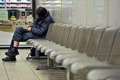 A man dozes off at a railway waiting room before the last train leaves. It is not only Japan's jobless who are sleeping at McDonald's for the price of a cup of coffee. Many with jobs, too, are bedding down cheaply in railway stations and comics cafes. The problem is particularly acute among the nation's temporary workers, working for low wages with near-zero job security. By one estimate, 45% of workers in Osaka Prefecture are temps, hired and fired with the weather.  (Yoshinori Mizuno)