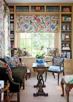 Built-in shelves and a window seat set a cozy stage in the library, accented by a colorful fabric from Lee Jofa. - Traditional Home ® / Photo: Emily Minton Redfield / Design: Joseph Minton