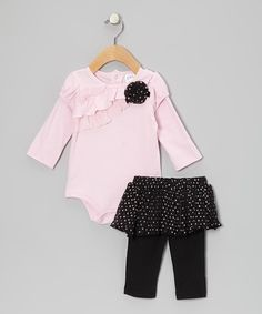 Full of pretty ruffled accents, a bow and classic print, this precious set is ready to keep little cuties twirling in style. Snaps in back of the tunic and an elastic waistband on the skirted leggings make slipping it on breezy and simple.Includes tunic and leggingsTunic and leggings: 100% cottonTrim and skirt: 100% pol...