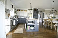 I love everything about this two toned kitchen. Love the microwave in the island and cubbies with baskets above cabinets. The blue/grey color of bottom cabinets is very timeless and neutral.