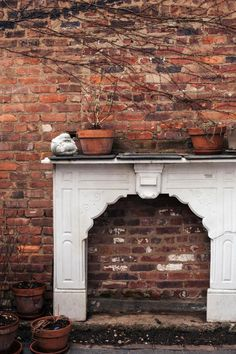 An old fireplace repurposed as shelving decor against a rustic brick wall