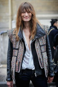 Caroline de Maigret in an embellished vest layered over a black moto jacket over a white tee