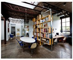 a contemporary slant to industrial/rustic - dark concrete floors, open bookshelves, modern clean-lined furniture with pops of color, white walls