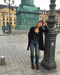 Jeanne Damas, maxi casaco preto, blusa preta listrada, calça jeans com barra desfiada, ankle boot marrom conhaque.