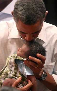 President Obama kisses the forehead of 3-week-old Ethan Muhire during a campaign stop in Marshalltown, Iowa