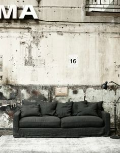Gray Sofa Against Peeling Wall