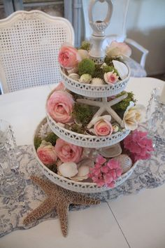 I love the roses mixed with the seashells and moss in this three tiered  display