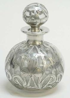 Clear glass perfume bottle with sterling silver overlay.