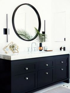 A sharp vanity, vertical sconces, and geometric terrariums are rounded out by the perfect circle...