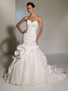 AA062 Sweetheart neckline wedding dresses has ruched bodice combined with crystal hand-beaded lace that showcases an asymmetrically dropped waistline.  Displays a tulle and lace underskirt framed by rich bustled taffeta that flows into a pick-up chapel train.