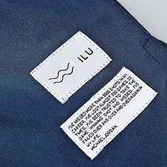 I don't like the idea of having two labels, but I've pinned this image because I like how its been stitched onto the material... its almost dot stitching. It doesn't take your attention off the words and onto the stitch.