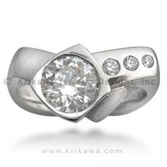"Modern Crossover Engagement Ring - This modern engagement ring is asymmetrical, and the lines are slightly organic without being ""floral."" The shank, or band, is squared off at all four corners. This style, called the European shank, can help prevent the ring from spinning around the finger.  3mm wide.  Ideal cut accent diamonds."