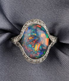 Art Deco Platinum, Black Opal, and Diamond Ring, set with an oval cabochon black opal measuring approx. 13.20 x 10.70 x 3.40 mm, framed by single-cut diamond melee, millegrain and engraved accents, size 5 1/2, maker's mark.