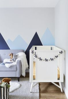 DIY Mountain mural for a nursery using painter's tape and two different tones of blue. A simple way to bring your walls to life!
