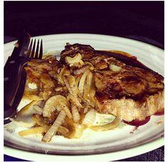 Medium rare steak with sautéed mushrooms and onions.