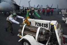 INDIAN OCEAN (June 7, 2013) Marines assigned to the Death Rattlers of Marine Fighter Attack Squadron (VMFA) 323 move nitrogen tanks on the flight deck of the aircraft carrier USS Nimitz (CVN 68). Nimitz Strike Group is deployed to the U.S. 7th Fleet area of responsibility conducting maritime security operations and theater security cooperation efforts.