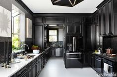 Black and Silver Iridized Chrysalis tiles from Ann Sacks peak out between Black Harlowe cabinetry by Kraftmaid. Whirlpool's 4-door refrigerator in Black Ice. Valspar's Ultra White for the floor and ceiling.