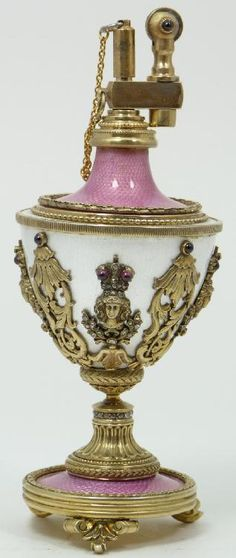 "Imperial Russian Faberge enameled silver lighter. Exquisitely guilloche enameled throughout with pink and pearlescent white. Stunning scrolled floral designs to body with ruby and diamond jeweled crowned busts. Gold wash Interior. Bottom holds Nicolai Schepelew work master hallmarks and 84 silver purity with town marks. Includes fitted wooden presentation box. Measures 6 1/8"" height x 2 1/2"" diameter (15.5cm x 6.3cm). Total weight of 7.5ozt/235grams."