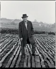 Seamus Heaney at a turf bog in Bellaghy wearing his father's coat, hat and walking stick (Bobbie Hanvey Photographic Archives, John J. Burns Library, Boston College)