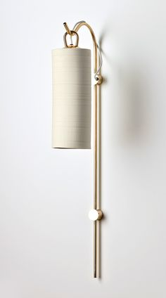 Elegantly playful yet dramatic, the Staff wall sconce features a solid brass staff, elongated proportions and a fluid hook detail. Long cylindrical porcelain shades feature inlay banding that, when lit, becoming translucent and provide a gorgeous banded glowing light.
