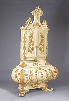 A fine Italian Rococo parcel gilt and paint decorated secretary cabinet, Venice, mid 18th century.