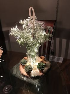 Just practicing. Baby's breath mason jar with fairy lights and succulents in tiny pots on tree slice disk centerpiece.