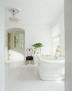 A Shimmery White Bathroom:  All the surfaces in the bath have a shimmery luster. White milk-glass walls are reflective; the floor is glass mosaic. Even the fabric used for the blinds has a thin gold Lurex thread running through it. The Waterworks fittings have a finish that's between gold and silver.  Only the green adds accent.