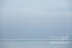 Small sailboats on the horizon on a cloudy day