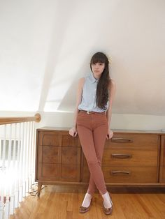 Sleevless button-up + high-waisted pants.  + Long hair.  + Shoes.