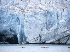 A glacier looms over sea kayakers as they make their way through the waters of the Svalbard archipelago in Norway. [Photograph by Frilet Patrick, hemis.fr/Getty Images]